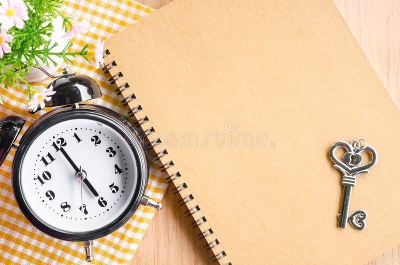 Εστίαση στο μαύρο ξυπνητήρι και το καφετί ημερολόγιο στοκ φωτογραφίες