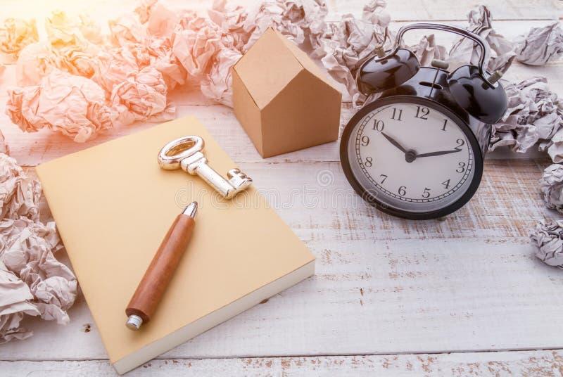 Εστίαση στο μαύρο ξυπνητήρι και το καφετί ημερολόγιο στοκ εικόνες