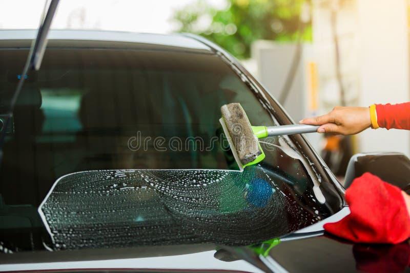 Εστίαση Selcective στο προσωπικό που χρησιμοποιεί το ελαστικό μάκτρο για να καθαρίσει τον ανεμοφράκτη στοκ εικόνες