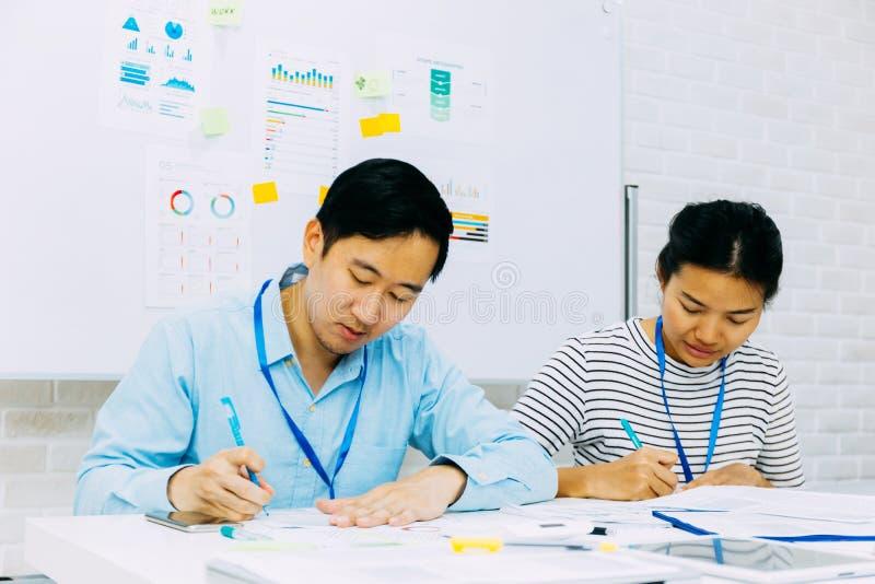 Εστιασμένοι εθνικοί συνεργάτες που κάνουν έρευνα ενώ κάθονται και γράφουν στο τραπέζι του γραφείου στοκ φωτογραφία