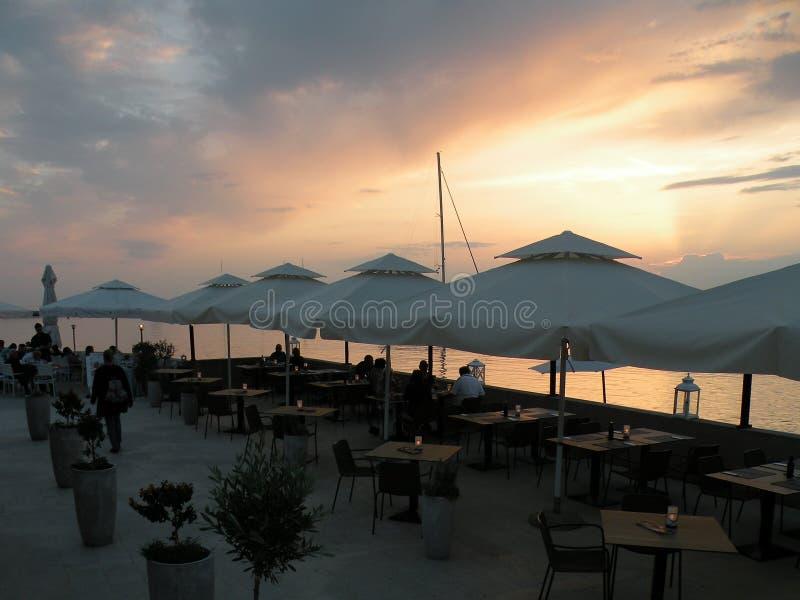 Εστιατόριο από τη θάλασσα με το ηλιοβασίλεμα, άνθρωποι στο γεύμα, πίνακες κάτω από τις άσπρες ομπρέλες Η μεσογειακή σκηνή των δια στοκ φωτογραφία