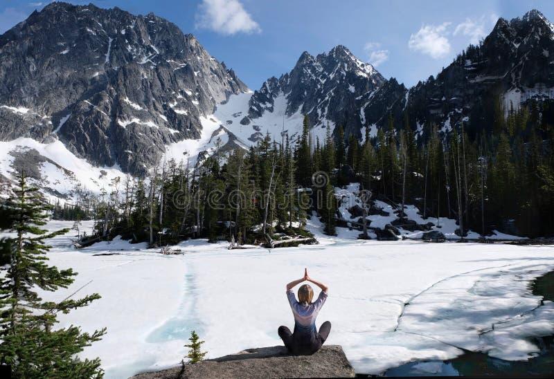 Εσωτερικά ειρήνη και mindfulness Γυναικών στη φυσική ακτή λιμνών με την όμορφη άποψη των χιονισμένων βουνών στοκ εικόνα