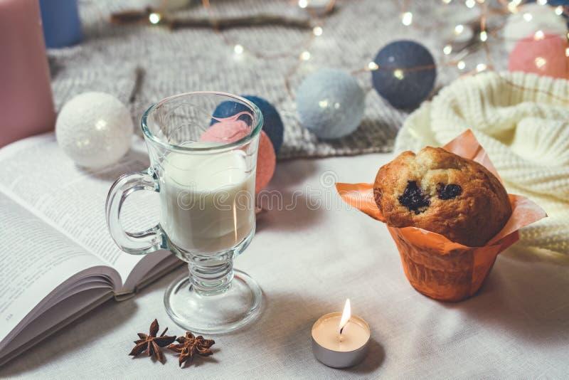 Εσωτερική άποψη ύφους ρομαντικού χειμώνα και του νέου έτους με ένα κερί, ένα βιβλίο, μια γιρλάντα, ένα κέικ και ένα ποτήρι του γά στοκ εικόνα με δικαίωμα ελεύθερης χρήσης