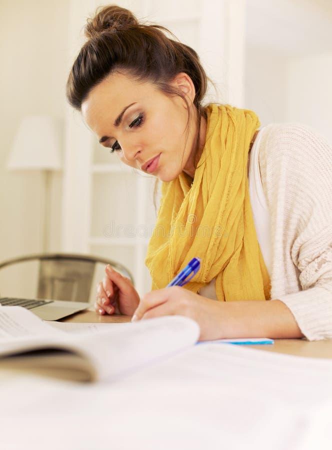 Εσωτερική γυναίκα που μελετά στο σπίτι να γράψει κάτι στοκ εικόνες