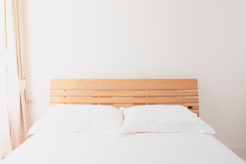 Εσωτερική σύγχρονη άσπρη διακόσμηση κρεβατοκάμαρων με τις μπεζ κουρτίνες μέσα στοκ εικόνες