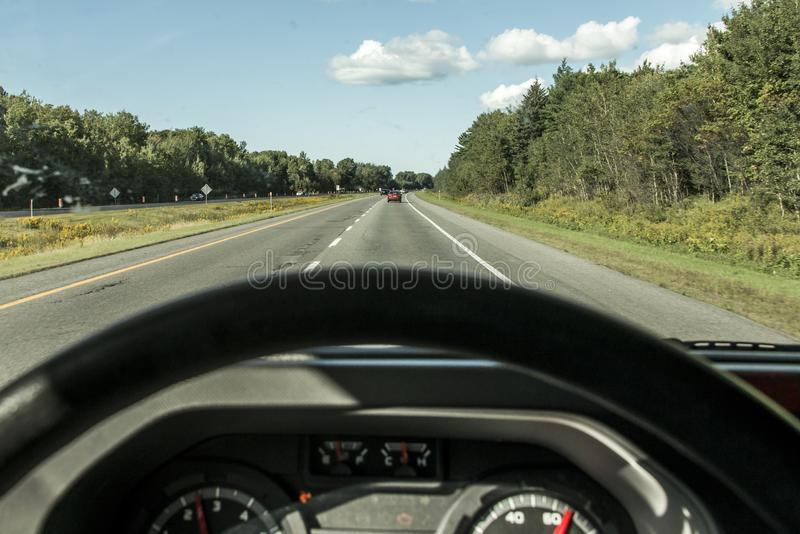Εσωτερική POV άποψης μεταφορά οδικού ζωηρόχρωμη υποβάθρου κυκλοφορίας τιμονιών και τροχόσπιτο έννοιας ταξιδιού επάνω δια τον Κανα στοκ εικόνες