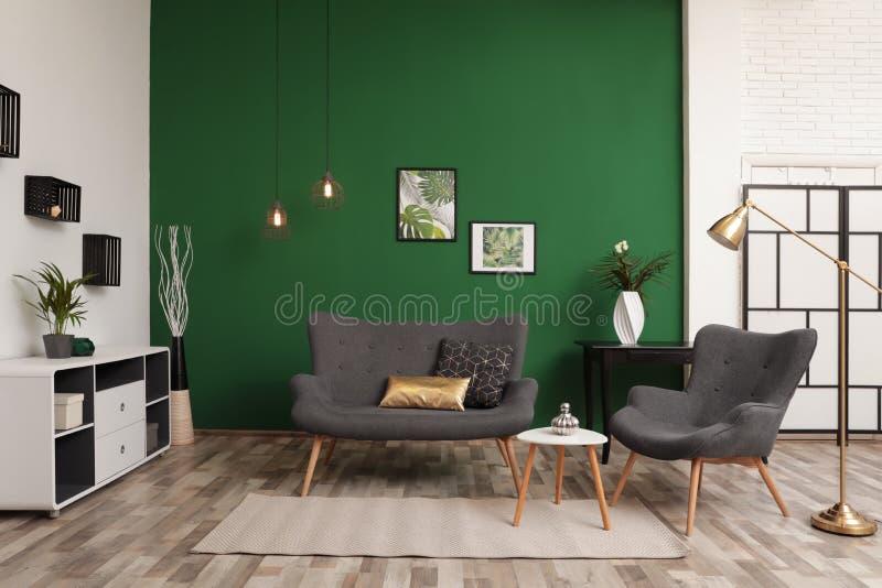Εσωτερικός μοντέρνος καναπές καθιστικών κοντά στον πράσινο τοίχο στοκ φωτογραφία με δικαίωμα ελεύθερης χρήσης