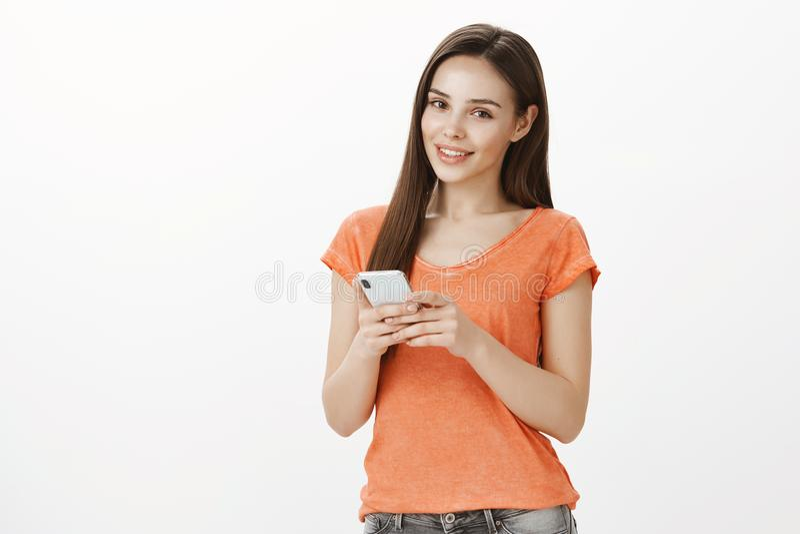 Εσωτερικός πυροβολισμός της ικανοποιημένης ξένοιαστης γοητευτικής γυναίκας στο κατάστημα, στεμένος με το smartphone και κοιτάζοντ στοκ φωτογραφίες με δικαίωμα ελεύθερης χρήσης