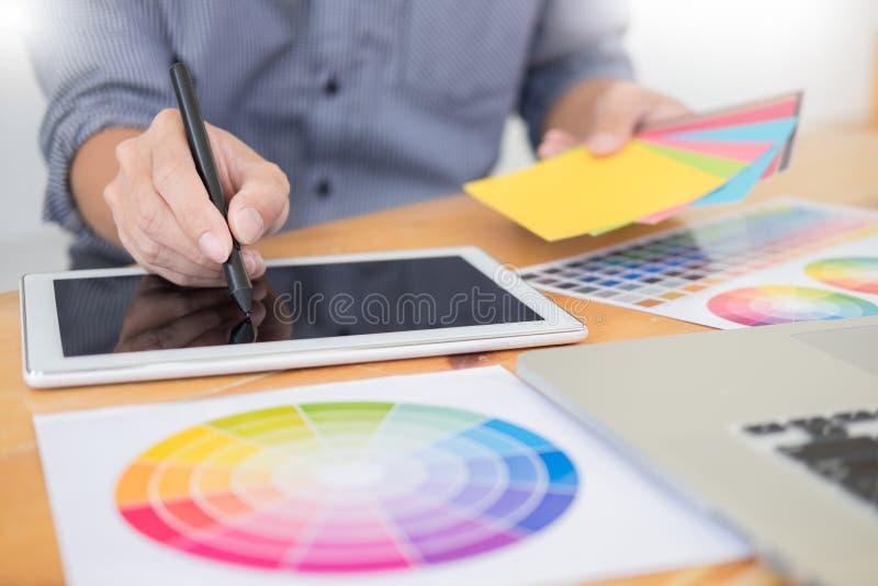 Εσωτερικός σχεδιαστής ομάδας που σύρει ένα νέο πρόγραμμα χρησιμοποιώντας το γραφικό υπολογιστή και επιλέγοντας swatch χρώματος τα στοκ φωτογραφία με δικαίωμα ελεύθερης χρήσης