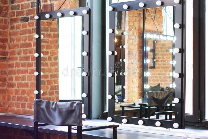Εσωτερικό βεστιάριο με μια καρέκλα, έναν πίνακα, έναν καθρέφτη και ένα φως σε ένα στούντιο φωτογραφιών στοκ φωτογραφία