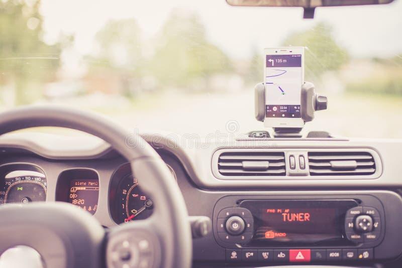 Εσωτερικό ενός σύγχρονου αυτοκινήτου μια ηλιόλουστη ημέρα Smartphone στο κινητό υποστήριγμα, που χρησιμοποιείται ως συσκευή ναυσι στοκ φωτογραφία