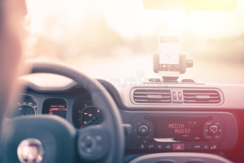 Εσωτερικό ενός σύγχρονου αυτοκινήτου μια ηλιόλουστη ημέρα Smartphone στο κινητό υποστήριγμα, που χρησιμοποιείται ως συσκευή ναυσι στοκ εικόνες με δικαίωμα ελεύθερης χρήσης