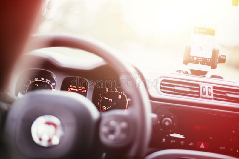 Εσωτερικό ενός σύγχρονου αυτοκινήτου μια ηλιόλουστη ημέρα Smartphone στο κινητό υποστήριγμα, που χρησιμοποιείται ως συσκευή ναυσι στοκ φωτογραφίες