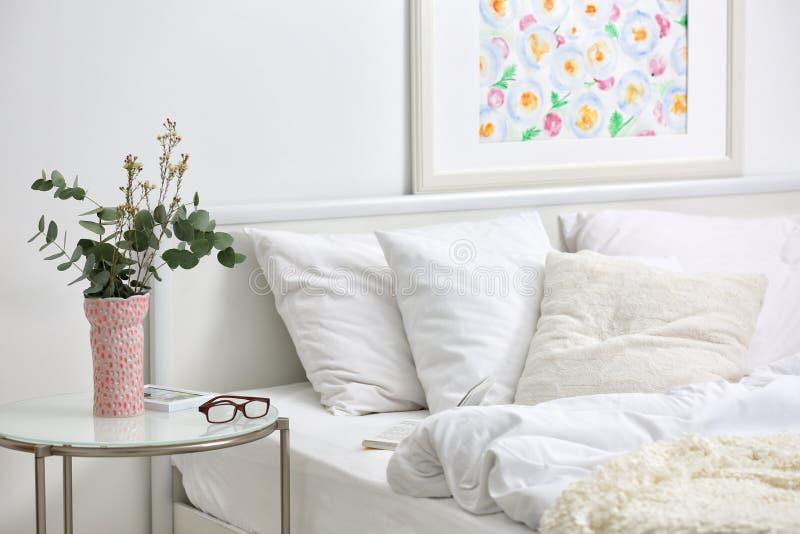 Εσωτερικό κρεβατοκάμαρων με το κρεβάτι και τα λουλούδια στοκ φωτογραφίες