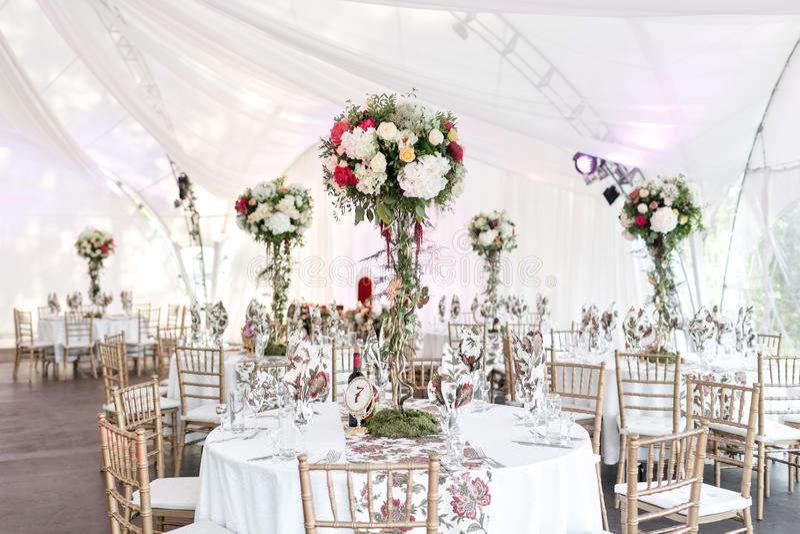 Εσωτερικό μιας διακόσμησης γαμήλιων σκηνών έτοιμης για τους φιλοξενουμένους Εξυπηρετημένος γύρω από τον πίνακα συμποσίου υπαίθριο στοκ φωτογραφίες με δικαίωμα ελεύθερης χρήσης