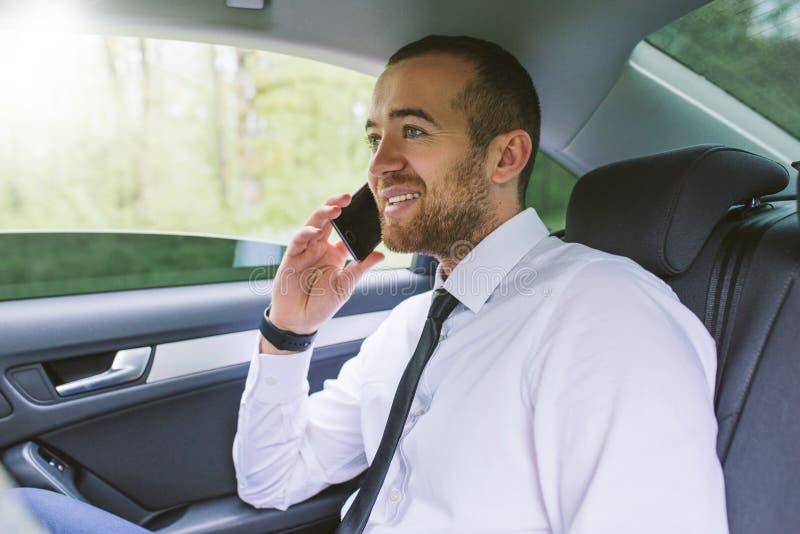 Εσωτερικό πορτρέτο ενός ευτυχούς επιχειρησιακού ατόμου που μιλά στην κινητή τηλεφωνική συνεδρίαση σε ένα πίσω κάθισμα αυτοκινήτων στοκ εικόνες με δικαίωμα ελεύθερης χρήσης