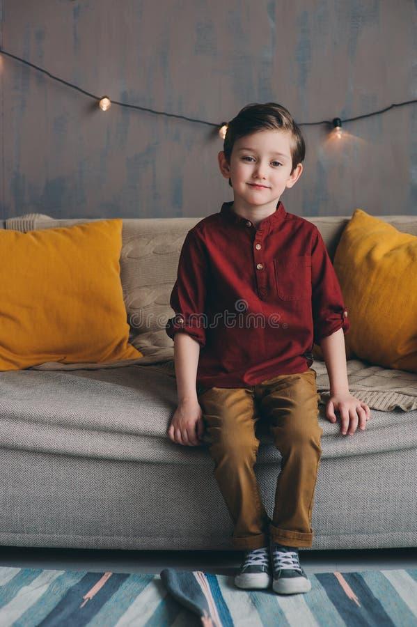 εσωτερικό πορτρέτο της ευτυχούς όμορφης μοντέρνης συνεδρίασης αγοριών παιδιών στον άνετο καναπέ στοκ εικόνα με δικαίωμα ελεύθερης χρήσης