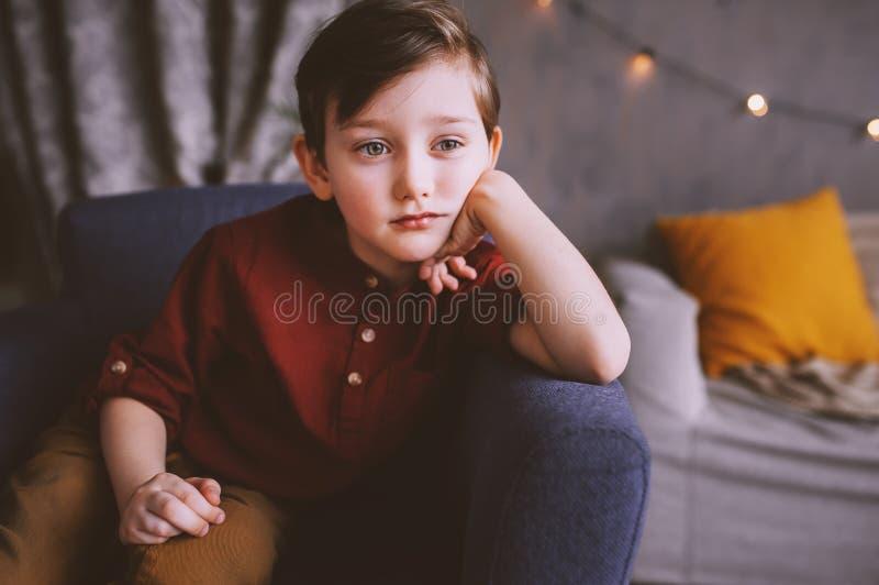 εσωτερικό πορτρέτο της ευτυχούς όμορφης μοντέρνης συνεδρίασης αγοριών παιδιών στον άνετο καναπέ στοκ εικόνα