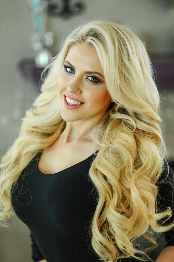 Εσωτερικό πορτρέτο της νέας ελκυστικής ξανθής γυναίκας με τη σύνθεση glamor και το κυματιστό hairstyle στοκ φωτογραφία
