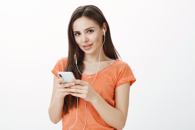 Εσωτερικό πορτρέτο του στοχαστικού δημιουργικού θηλυκού με την ελκυστική εμφάνιση, που κρατά το smartphone, μουσική ακούσματος μέ στοκ φωτογραφία