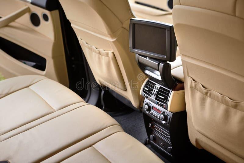 Εσωτερικό στο δέρμα χρωμάτων κρέμας του σύγχρονου αυτοκινήτου πολυτέλειας γοήτρου Επίδειξη στροφέων για τον επιβάτη πίσω θέσεων στοκ εικόνες