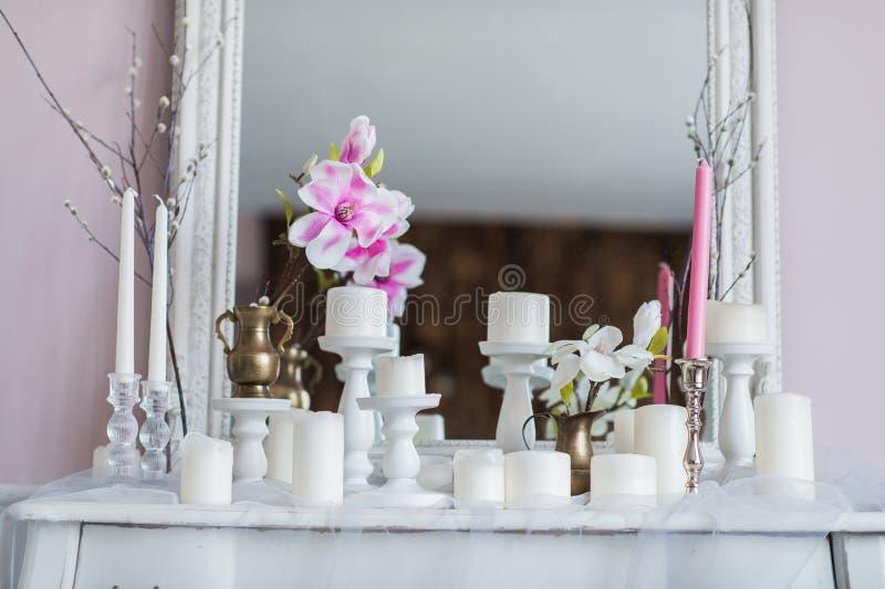 Εσωτερικό σχέδιο του άσπρου δωματίου με τα όμορφα λουλούδια στον εξυπηρετούμενο πίνακα Μεγάλος δημιουργικός κλασσικός καθρέφτης στοκ φωτογραφίες με δικαίωμα ελεύθερης χρήσης