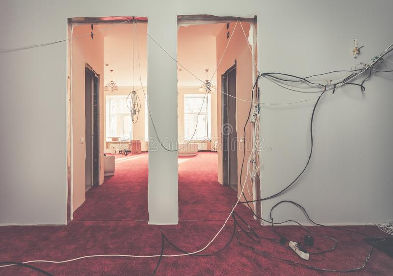 Εσωτερικό της αίθουσας του διαμερίσματος με τα προσωρινά ηλεκτρικά καλώδια κατά τη διάρκεια της βελτίωσης ή της αναδιαμόρφωσης, α στοκ εικόνες