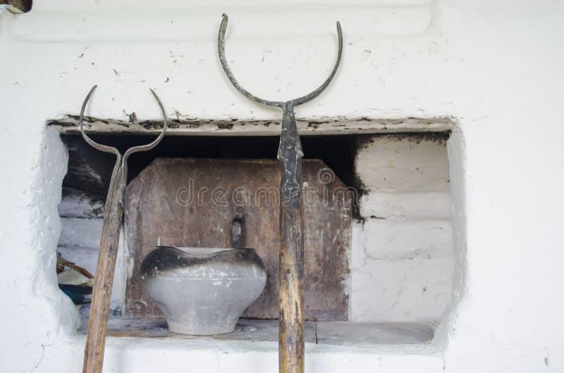 Εσωτερικό της κουζίνας στο παλαιό του χωριού σπίτι με τον παραδοσιακό φούρνο τούβλου που θερμαίνεται από το ξύλο και το σκεύος γι στοκ εικόνα με δικαίωμα ελεύθερης χρήσης