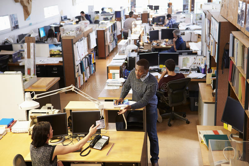 Εσωτερικό του γραφείου του πολυάσχολου αρχιτέκτονα με την εργασία προσωπικού στοκ φωτογραφία