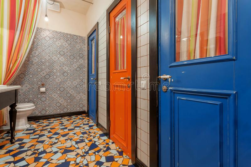 Εσωτερικό του εκλεκτής ποιότητας δωματίου τουαλετών ύφους με τις παλαιές ξύλινες πόρτες στο λουτρό Μπλε και κόκκινες πόρτες πέρα  στοκ εικόνες με δικαίωμα ελεύθερης χρήσης