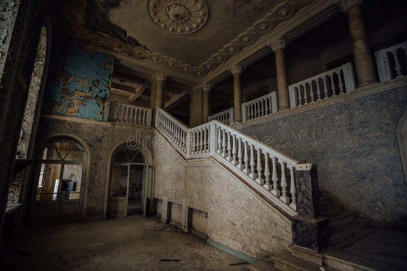 Εσωτερικό του παλαιού ανατριχιαστικού εγκαταλειμμένου μεγάρου Σκάλα και κιονοστοιχία στοκ εικόνες
