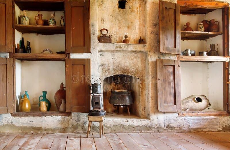Εσωτερικό του παλαιού σπιτιού στη χώρα της Γεωργίας, με τα εργαλεία κουζινών, την κατσαρόλα, το primus, την εστία και το ξύλινο π στοκ εικόνες