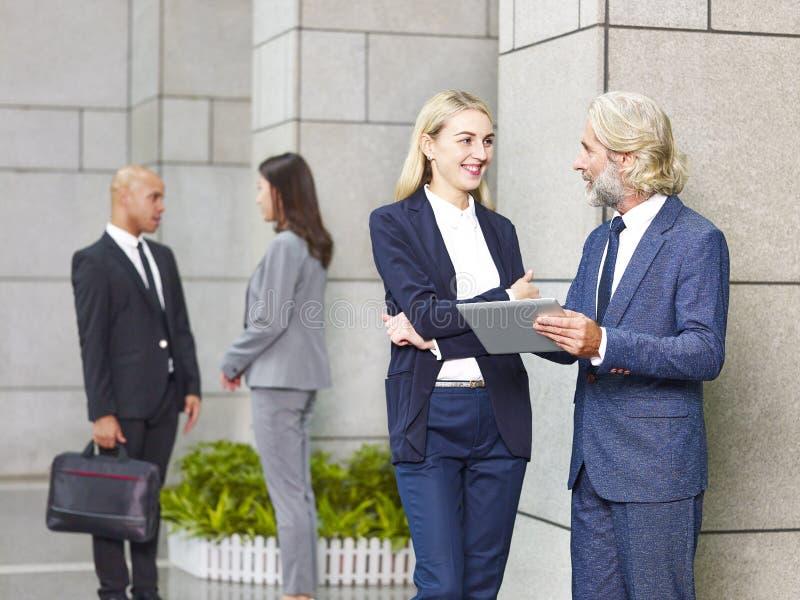 Εταιρικοί επιχειρηματίες που στέκονται την ομιλία στοκ φωτογραφίες