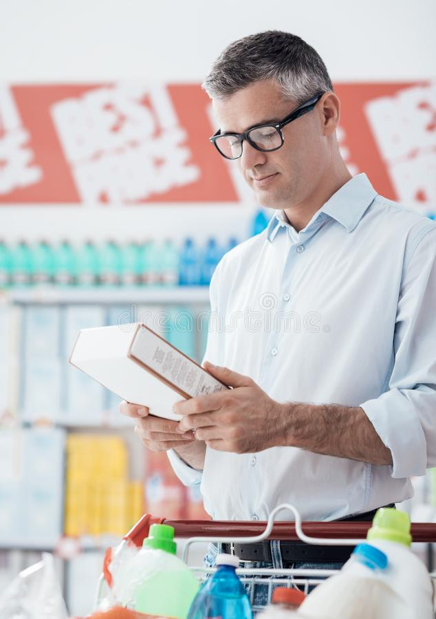 Ετικέτες τροφίμων ανάγνωσης ατόμων στοκ εικόνες με δικαίωμα ελεύθερης χρήσης