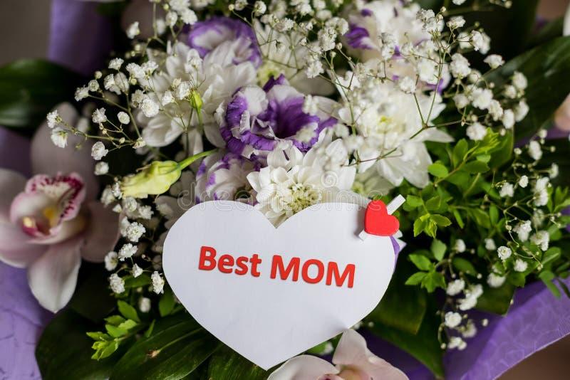 Ετικέττα δώρων με το κείμενο καλύτερο Mom από μια ανθοδέσμη των τριαντάφυλλων και ένα τυλιγμένο παρόν για την ημέρα μητέρων `, γε στοκ εικόνα