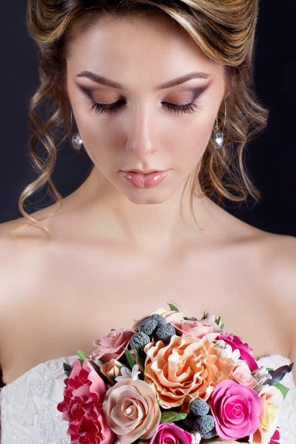 Ευγενές πορτρέτο των ευτυχών χαμογελώντας όμορφων προκλητικών κοριτσιών στο άσπρο γαμήλιο φόρεμα με μια γαμήλια ανθοδέσμη υπό εξέ στοκ εικόνες