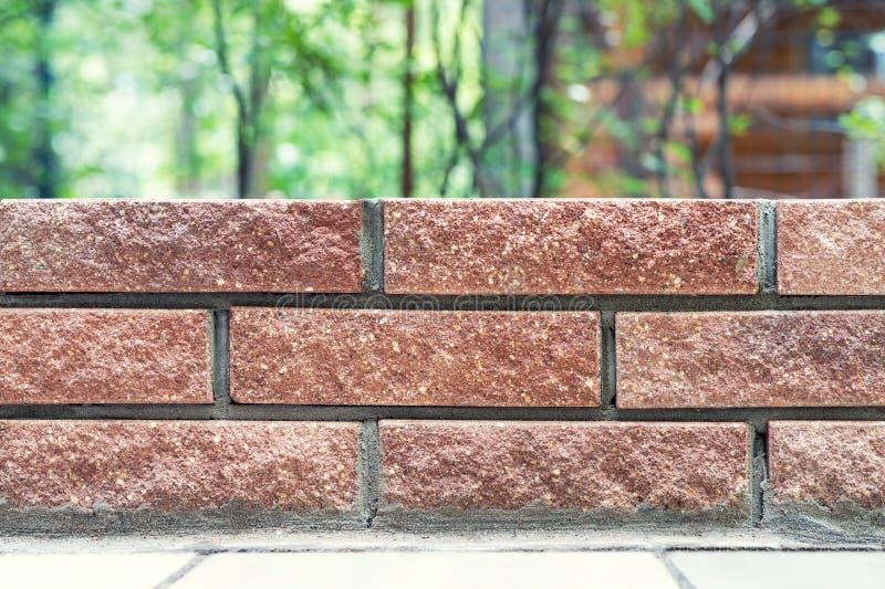Ευθείες γραμμές νέου φρέσκου τοίχου πλινθοδομής με το θολωμένο κατώφλι πάρκων ή σπιτιών στο υπόβαθρο Σύγχρονος τουβλότοιχος υπαίθ στοκ φωτογραφίες