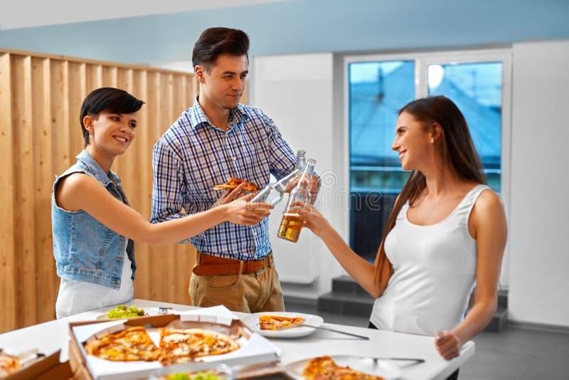 Ευθυμίες Ευτυχή μπουκάλια μπύρας φίλων ενθαρρυντικά στο εσωτερικό συμβαλλόμενο μέρος cele στοκ φωτογραφία με δικαίωμα ελεύθερης χρήσης