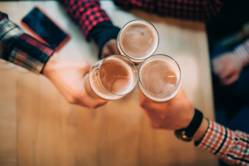 Ευθυμίες Τοπ άποψη κινηματογραφήσεων σε πρώτο πλάνο των φίλων που κρατούν τις κούπες με την μπύρα στοκ φωτογραφίες