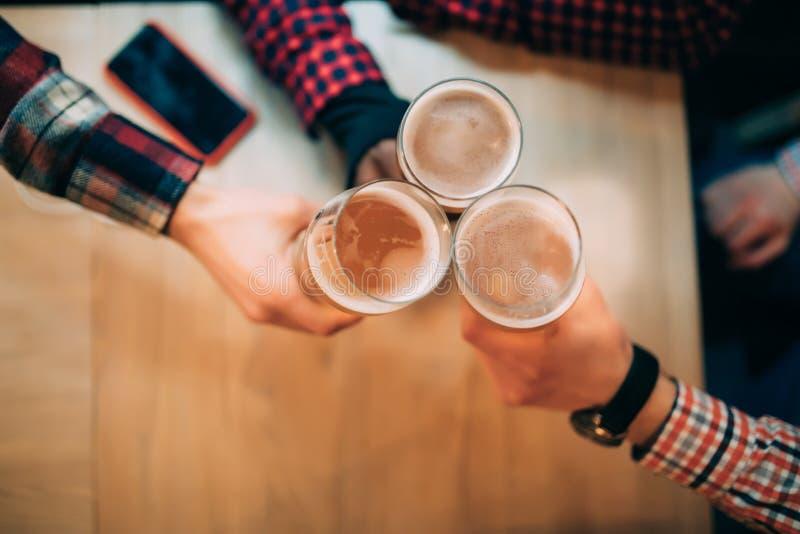 Ευθυμίες Τοπ άποψη κινηματογραφήσεων σε πρώτο πλάνο των φίλων που κρατούν τις κούπες με την μπύρα στοκ φωτογραφία με δικαίωμα ελεύθερης χρήσης