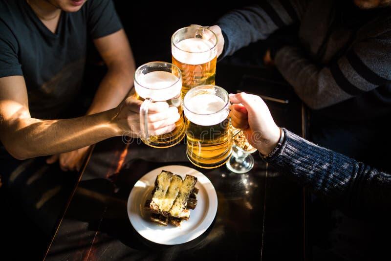 Ευθυμίες Τοπ άποψη κινηματογραφήσεων σε πρώτο πλάνο των ανθρώπων που κρατούν τις κούπες με την μπύρα στοκ εικόνα με δικαίωμα ελεύθερης χρήσης