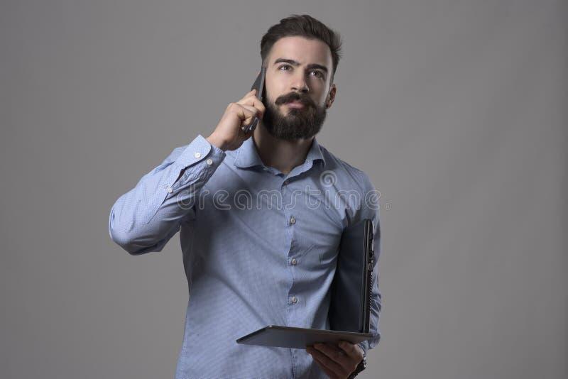 Ευμετάβλητο πορτρέτο της νέας γενειοφόρου ταμπλέτας, του lap-top και της ομιλίας εκμετάλλευσης επιχειρηματιών στο τηλέφωνο στοκ εικόνες
