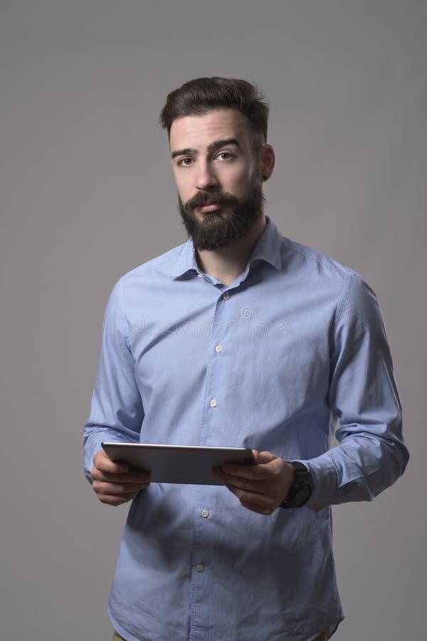 Ευμετάβλητο πορτρέτο του σοβαρού βέβαιου νέου γενειοφόρου υπολογιστή και της εξέτασης ταμπλετών εκμετάλλευσης επιχειρησιακών ατόμ στοκ φωτογραφία με δικαίωμα ελεύθερης χρήσης