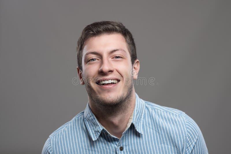Ευμετάβλητο πορτρέτο του γελώντας νέου υπερήφανου επιχειρηματία που εξετάζει τη κάμερα στοκ εικόνες