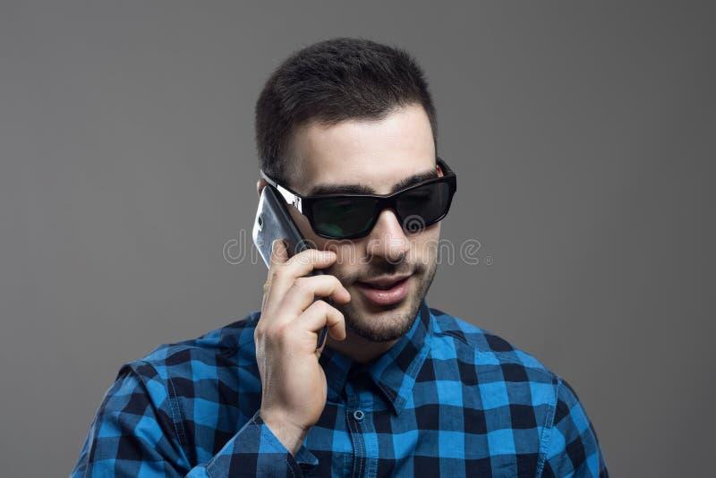 Ευμετάβλητο πορτρέτο του νεαρού άνδρα που φορά τα γυαλιά ηλίου που μιλούν στο τηλέφωνο κυττάρων που κοιτάζει κάτω στοκ φωτογραφίες