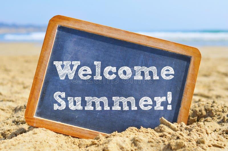 Ευπρόσδεκτο καλοκαίρι κειμένων σε έναν πίνακα κιμωλίας, στην άμμο μιας παραλίας στοκ εικόνες με δικαίωμα ελεύθερης χρήσης