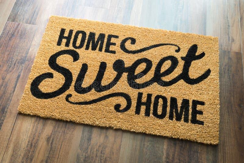 Ευπρόσδεκτο χαλί εγχώριων γλυκό σπιτιών στο πάτωμα στοκ φωτογραφία