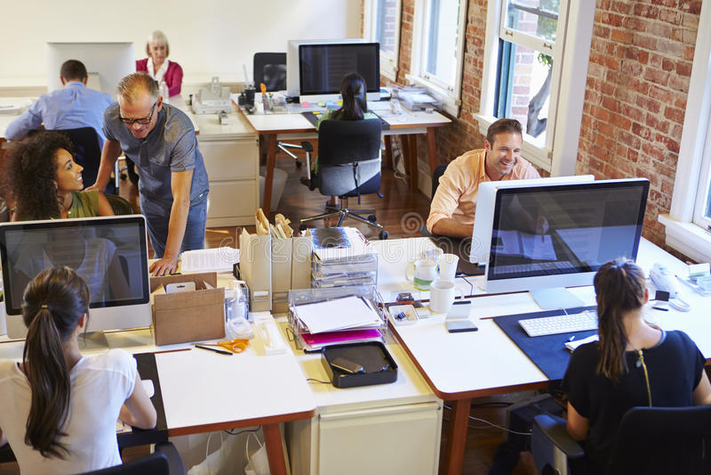 Ευρεία άποψη γωνίας του πολυάσχολου γραφείου σχεδίου με τους εργαζομένους στα γραφεία στοκ εικόνες με δικαίωμα ελεύθερης χρήσης