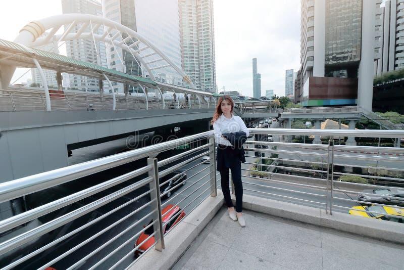 Ευρεία γωνία που πυροβολείται της βέβαιας νέας ασιατικής εξέτασης επιχειρησιακών γυναικών στη κάμερα το αστικό υπόβαθρο πόλεων στοκ εικόνες