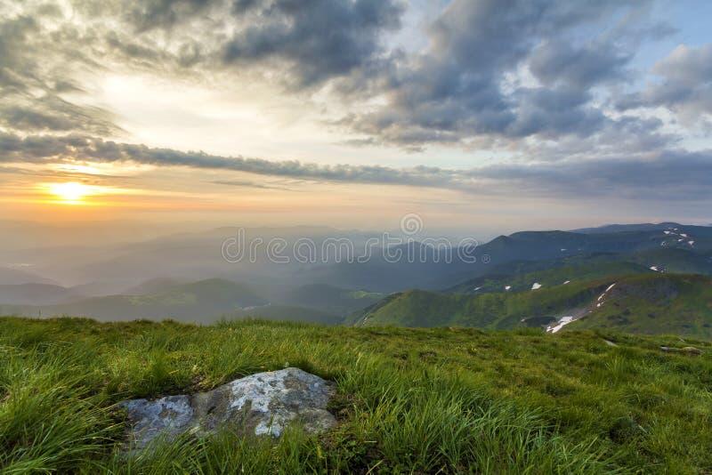 Ευρεία θερινή θέα βουνού στην ανατολή Καμμένος πορτοκαλής ήλιος που αυξάνει στον μπλε νεφελώδη ουρανό πέρα από τον πράσινο χλοώδη στοκ εικόνες με δικαίωμα ελεύθερης χρήσης